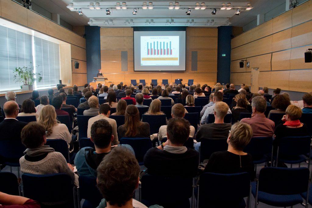 Podiumsdiskussion und Vortrag eines Wissenschaftlers vor Publikum.